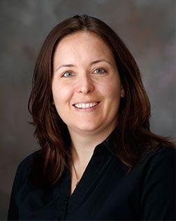 Lori Romano: Smiling woman with brown hair.